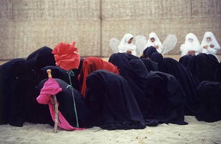 Hazreti Muhammed'in torunu Hz. Hüseyin'in ve beraberindeki 72 kişinin Muaviye'nin oğlu Yezid'in ordularınca Kerbela'da şehit edilmesi olayı her yıl 10 Muharrem'de canlandırılır. Şehitlerin anıldığı, yas tutulan bu olayın adı Ta'ziye'dir. Ta'ziye, İslam'daki tek dram türüdür. Ta'ziye'de kullanılan siyah giysiler yası, beyazlar kefeni, kırmızı şehitlerin kanını, kuma saplanmış kılıç katliamın aracını, arka planda görülen kanatlı, beyaz giysili çocuklar Kerbela'da katledilen masum çocukları simgeler. Şii inancına göre, katliamdan sonra alan çiçek tarlasına dönüşmüştür. Bu sebeple, Ta'ziye'de mutlaka çiçeklere yer verilir. Caferiler geleneksel olarak, Kerbela'nın acısını sırtlarını zincirlerle döverek hissetmek isterler. Fotoğraf: Ercan Arslan