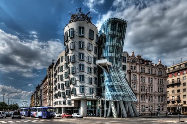 Dans Eden Ev/Dancing House, Prag, Çek Cumhuriyeti. 1895 yılında Yeni Rönesans tarzında yapılan bina 1945 yılında yanlışlıkla ABD uçakları tarafından bombalanmış ve yeri uzun zaman boş kalmış. 1989'daki devrimden sonra dikkat çekici bir köşe tasarlanmasına karar verilmiş. Proje önce Hırvat ve Çek kökenli bir mimar olan Vlado Milunic ile 1992 yılında başlamış. Daha sonra Kanada kökenli ünlü mimar Frank Gehry projeye dahil olmuş. İlk tasarlanan silindir binayı fazla erkeksi bulan Gehry, onun yanına yumuşak hatlı bir kadın silueti eklemiş. Gehry, binaya Fred & Ginger adını vermeyi düşünmüş ama bu fikrinden vazgeçmiştir. Fakat Dancing House yine de Fred & Ginger adıyla da bilinir. Yapının, şehrin tarihi ve mimari dokusuna uygun olmadığını söyleyip karşı çıkanlar çok olmuştur ama bina, Prag'ın sembollerinden biri haline gelmiştir. Mimarlar ise binayı Yeni Barok olarak adlandırmışlardır. Farklı tarzıyla dikkat çeken bu yapı, uluslararası şirketlerin ofisleri olarak kullanılmakta, çatı katında bir restoran bulunmaktadır. Gehry, bir teknolojiyi bir başkasıyla mantığa aykırı bir biçimde yan yana getirerek eski bağlılıklar ve tutarlılıklarla alay etmeyi sever: Geleneksel biçimlerin komik çözülmesi, bozuşturma ve çarpıtma aracılığıyla komikleştirilir. Gehry, ikonik yapıları, kendine has estetik anlayışı, tasarıma kazandırdığı yeni ifade biçimi, kullanılan materyaller konusundaki yeni arayışları, şehirleşmedeki sosyal ve kültürel rolü ile mimarinin önde gelen simalarından biridir. Fotoğraf:www.3oda1salon.net