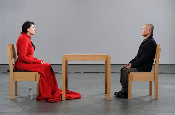 Sanatçı Aramızda, Marina Abramovic, 2010. New York'taki Modern Museum of Art'ta (MoMA) her gün halka açık olarak gerçekleştirilen bu Performans üç aydan fazla devam etti. Abramovic, avlunun ortasına yerleştirilen küçük, ahşap bir masaya oturmuştu; yüzünde kayıtsız bir ifade vardı. Ziyaretçilerden arzu eden sanatçının karşısına oturuyordu. Sessizce, yüz yüze bakışıyor, bu sırada gelişen çeşitli duyguları anlatmaları bekleniyordu. Bazıları sanatçının sessizliğini bir meydan okuma, kışkırtıcı bir tavır olarak görüyor; bazıları performansın altında derin bir keder algılayıp ağlamaya başlıyordu. Abramovic'in karşısına oturanlardan biri de Lady Gaga oldu. Abramovic'e göre, normal şartlarda müzeye gitmeyen, Performans Sanatı hakkında hiçbir şey bilmeyen, bu sanata önem vermeyenler bile Lady Gaga'dan ötürü izlemeye geldiler. Facebook'ta Marina ile Oturmak adlı bir sayfa açıldı. Bu süre boyunca sayfanın bir milyona yakın ziyaretçisi oldu. Fiziksel ve zihinsel sınırları zorlayan çalışmaları ile tanınan Abramovic, 2005 yılında Joseph Beuys'un 1965 tarihli Ölü Bir Tavşana Resimler Nasıl Anlatılır? Performansını yorumlamıştı. Abramovic, Beuys'tan başka da pek çok sanatçının gerçekleştirdiği ikonik performansları yeniden yorumladı. Abramovic 1976'da Alman sanatçı Ulay ile tanışmış ve on yıldan uzun bir süre birlikte çalışmışlardı. Marina Abramovic'in büyük aşkı Ulay'dan ayrılması da bir Performans ile gerçekleşti. Doksan gün süren bir Performans ile Çin Seddi'nde ayrıldılar. 1988 yılında Aşıklar adlı performanslarında Marina ve Ulay Çin Seddi boyunca üç ay yürümüştü. Bu yürüyüş onların ayrılığını temsil ediyordu. Tekrar birbirlerini görmeleri de Abramovic'in Sanatçı Aramızda adlı Performansında yirmi küsur yıl sonra gerçekleşti. Fotoğraf:www.popmatters.com