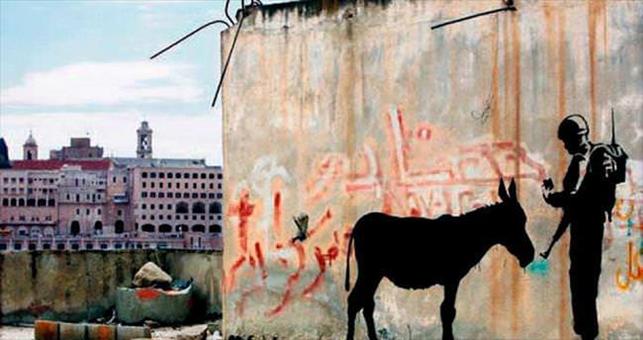 Banksy, 10 yıldır başta İngiltere olmak üzere farklı ülkelerde yaptığı çarpıcı duvar resimleriyle ünlenen bir sanatçı.  Gerçek kimliği yakın zamana kadar bilinmiyordu. Banksy, eserlerinde kullandığı imzası.  Sanatını bir iletişim aracı olarak kullanan sanatçı, iletmek istediği birçok politik ve sosyal mesajı dünyanın en kalabalık şehirlerinde herkesin görebileceği alanlarda veriyor. Kendi ifadesiyle gerilla sanatçısı olan Banksy, çalışmalarında savaş karşıtı, çevreci, hayvan haklarını savunan ve tüketim çılgınlığını eleştiren mesajlar vermektedir. Çağdaş dönemde, sokak sanatçılarının eserleri açık artırmalarda yer buluyor. Banksy'nin çalışmaları, dünyanın dört bir yanındaki Çağdaş Sanat örneklerinin profesyonel koleksiyoncuları ve alıcıları, Hollywood ünlüleri tarafından koleksiyonlara dahil ediliyor. 2007 yılında Banksy'nin imzasını taşıyan çalışmalar açık artırmada 500.000 Sterline satılmıştı. İngiliz sokak sanatçısı Banksy'nin 2006'da İsrail'in Batı Şeria'da ördüğü duvar üzerine çizdiği resim, İsrail'deki sert güvenlik tedbirlerini eleştiriyor, İsrail askeri tarafından kimlik kontrolüne tabi tutulan bir eşeği gösteriyordu. Duvar resmi, üzerine çizildiği 4 tonluk duvar parçasıyla birlikte 2015'te ABD'de müzayedeye kondu. ABD'den önce, Londra'da sergilendi. Eserin taban fiyatı 700 bin dolar idi. Banksy, hicvettiği düzen tarafından baş tacı ediliyor. Fotoğraf:www.sabah.com.tr
