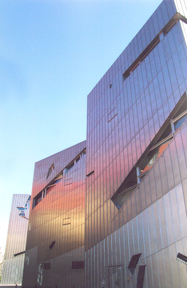 Yahudi Müzesi, 2001, Berlin, Almanya. Burası, Yahudilerin Almanya'daki 2000 yıllık yaşamını betimlemeyi hedefleyen bir müze. Mimarı, Daniel Libeskind (1946-). Yapısökümcü bu proje, önceden Batı Berlin Şehir Müzesi olan 18. yüzyıl yapımı Barok bir binanın yanında gerçekleştirildi. Libeskind'in binasının dışı çinko kaplı. Bina, içine girilebilen bir heykel gibi. Taban kesiti şimşek şeklinde. Beş katlı, on bin metrekarelik alanı kaplayan binayı, Davut yıldızının bozulmuş şekli olarak okuyorlar. Binanın içi labirent gibi. İçinde Soykırım Kulesi var. 20 metre yüksekliğindeki kuleye ağır, demir bir kapıdan giriliyor. Burası karanlık ve soğuk bir yer. 49 beton yükseltinin üzerine ağaç dikilmiş. Burası E. T. A Hoffman Bahçesi. Müze bir başyapıt olarak kabul ediliyor.  Uçan kirişlerin, yamuk döşeme ve duvarların mimarlığı, yitirenlerin, kaybedenlerin mimarlığıdır, deniyor.  Fotoğraf: Füsun Kavrakoğlu, 2004.