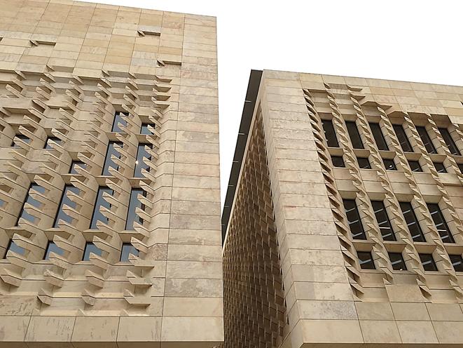 İki bloktan oluşan Parlamento'nun görünümünü hafifletmek ve mevcut yola uygunluk açısından bina oldukça ince sütunlar üzerinde yükseliyor. Bloklardan birinde parlamento, diğerinde ise parlamento üyelerinin ve başbakanın ofisleri bulunuyor. Cephe masif taş ile kaplı. Cephedeki taş çıkıntılar güneşin yönü göz önüne alınarak şekillendirilmiş. Güneş ışınlarını filtrelerken gün ışığını içeri alıyor. Bu parçaların her biri, makine ile yontulmuş. Şehrin tarihi yapısına ters düşmeyen ama en son teknolojiden de istifade eden bir yapı ortaya konmuş. Binanın taş olması sıcaktan korunma ve doğal havalandırma için tercih edilmiş. Ayrıca kullanılan taş, Malta kalkeri, tarihi binalarda da kullanılmış olduğu için yeni Parlamento binası çevre ile tamamen uyumlu olmuş. Taş ayrıca jeotermal ısı transferi için tercih edilmiş: 140 m derine, deniz seviyesinin 100 m altına inen 40 adet jeotermal kuyu yapılmış. Ayrıca, çatı güneş panelleri ile kaplanmış. Alınan bu önlemlerle bina kışın ısınma için gerekli enerjinin %80'ini, yazın soğutma için gerekli enerjinin %60'ını kendisi üretiyor. Fotoğraf: Füsun Kavrakoğlu