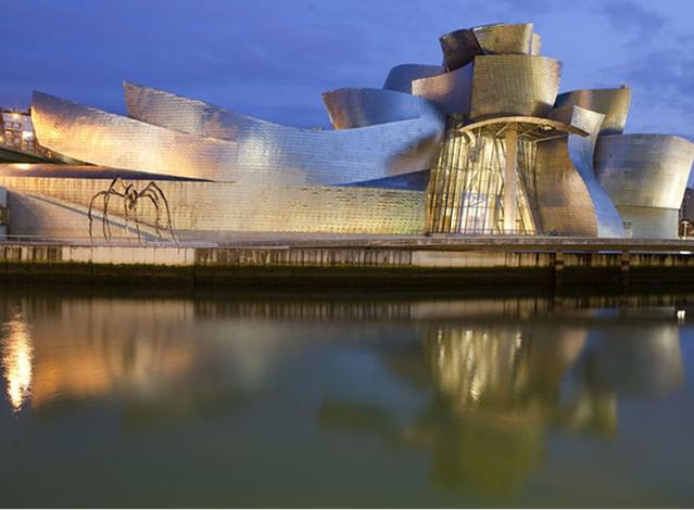 Bilbao Guggenheim Müzesi. İspanya'nın Bask Bölgesi'nde bulunan müze, Guggenheim Vakfı'nın dünyadaki beş müzesinden biridir. Mimari ile sanat arasındaki diyaloğu arttırmakla öne çıkmış, Pritzker Mimarlık Ödülü ve daha pek çok ödülün sahibi bir mimar olan Frank Gehry (1929-) tarafından tasarlanan ve 1997 yılında tamamlanan bu bina Yapısökümcü mimarinin ünlü bir örneğidir. Cephesi, balık ölçülerinde titanyum plakalarla kaplıdır. İspanya'nın küçük bir şehrine kurulmuş olan müzeyi yılda ortalama 800 bin kişi ziyaret ediyor ve şehrin adı neredeyse müzeyle birlikte anılıyor. Fotoğraf: www.insightguides.com/Corrie Wingate.