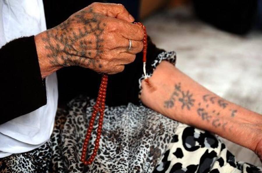 """""""Duyduğumuza göre yaptırdığımız dövmeler günahmış. Ahirette kerpetenle sökülecekmiş. Tabii bu bizi korkutuyor. Ancak, o zaman kimse günah olduğunu söylemedi. 50-60 yıl önce daha çok yaygındı. Dövmede kız çocuğu emziren anne sütü kullanıldığında ölene kadar çıkma ihtimali yoktur."""" """"Biz yaptırdıktan sonra günlerce yataktan kalkamazdık. Ateşimiz çıkardı."""" Fotoğraf: www.cnnturk.com/dovmenin-deq-hali"""