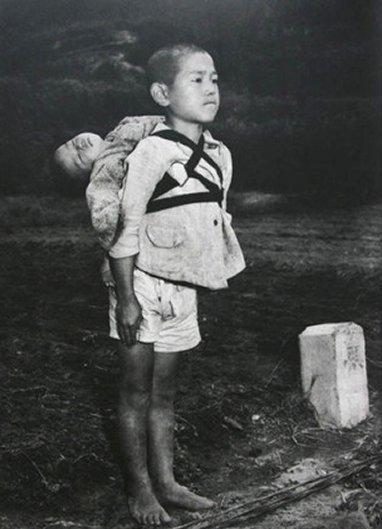 """1945 yılında Japonya'nın Nagazaki kentine atılan atom bombasının ardından çekilmiş bu fotoğrafta bir Japon çocuk sırtında ölü kardeşini taşırken görülüyor. Papa Francesco, bu fotoğrafı """"Savaşın Meyvesi"""" ibaresiyle Vatikan'ın nükleer silahlanmaya karşı olan tutumunu hatırlatmak için çoğaltınca bu acı kare gündeme geldi. Fotoğraf: Peru.com"""