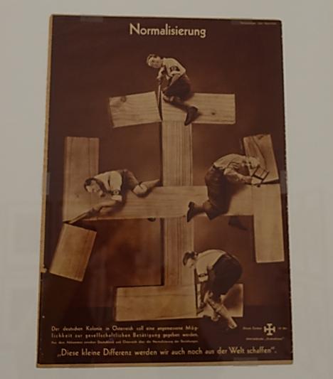 Normalleşme, John Heartfield (1891-1969), 1936. Eserin konusu Almanya ile Avusturya'nın iki yıl içinde birleşme kararıdır. Sanatçı Avusturya milliyetçiliğinin sembolü olan Kudüs Haçı'nın kenarlarını keserek bunun altındaki Nazi gamalı haçını gösteriyor. Fotoğraf: Füsun Kavrakoğlu, Tate Modern, Londra, 2017.
