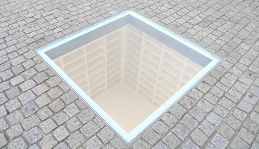 """Kitaplık, Micha Ullman, 1995. Kitap yakma denilince ilk akla gelenlerden biri 10 Mayıs 1933 felaketidir. Bu olayı unutturmamak için 1995 yılında İsrailli sanat profesörü ve heykeltıraş Micha Ullman (1939-) Bebelplatz'a Kitaplık adlı bir eser yapmış. En üstte parke taşların arasına yerleştirilmiş şeffaf bir cam var. Camdan, 20 bin kitabı alabilecek kapasitede bir kütüphanenin boş rafları görülüyor. Meydanda, Heinrich Heine'nin 1821 tarihli Almansor adlı oyunundan da bir alıntı var: """"Bu yalnızca bir başlangıç; kitapların yakıldığı yerde sonunda insanlar da yakılır."""" Anıta ek olarak her yıl Mayıs ayının başından 10'una kadar Humbolt Üniversitesi tarafından aynı meydanda edebiyat festivali düzenleniyor; festival boyunca meydana konan raflardan kitap alıp yerlerdeki minder ve hamaklarda okumak mümkün, aynı zamanda öğrenciler kitap satışı yapıyor ve kitap okuma etkinlikleri düzenleniyor. Fotoğraf: e-Skop"""